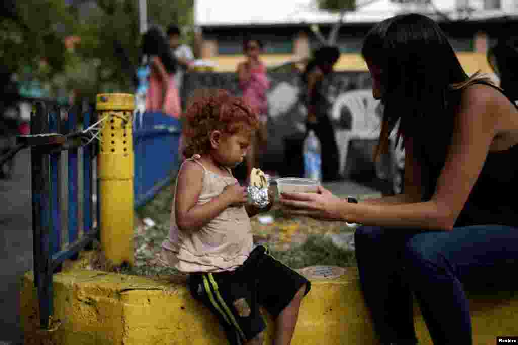 A volunteer for the Make a Difference (Haz La Diferencia) charity initiative gives a cup of soup and an arepa to a homeless child in on a street in Caracas, Venezuela.