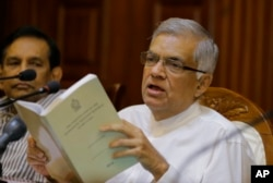 FILE - Sri Lanka's sacked prime minister Ranil Wickremesinghe holds a copy of the constitution of Sri Lanka as he attends a media briefing at his official residence in Colombo, Sri Lanka, Oct. 29, 2018.