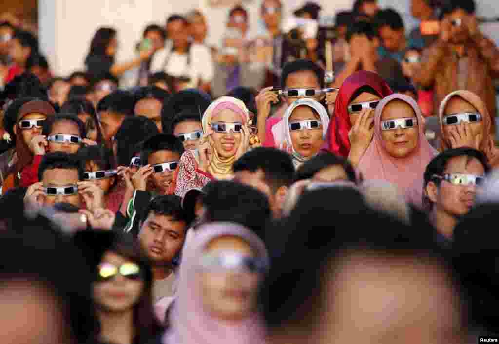 مردم با عینک های مخصوص، خورشید گرفتگی را در اندونزی تماشا می کنند.