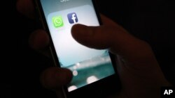 FILE - The WhatsApp and Facebook app icons are shown on an iPhone.