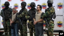 Venezuelan soldiers escort Colombian drug-trafficking boss Maximiliano Bonilla Orozco (R) and Gildardo de Jesús García Cardona, before being extradited to the United States, in Caracas on December 15, 2011.