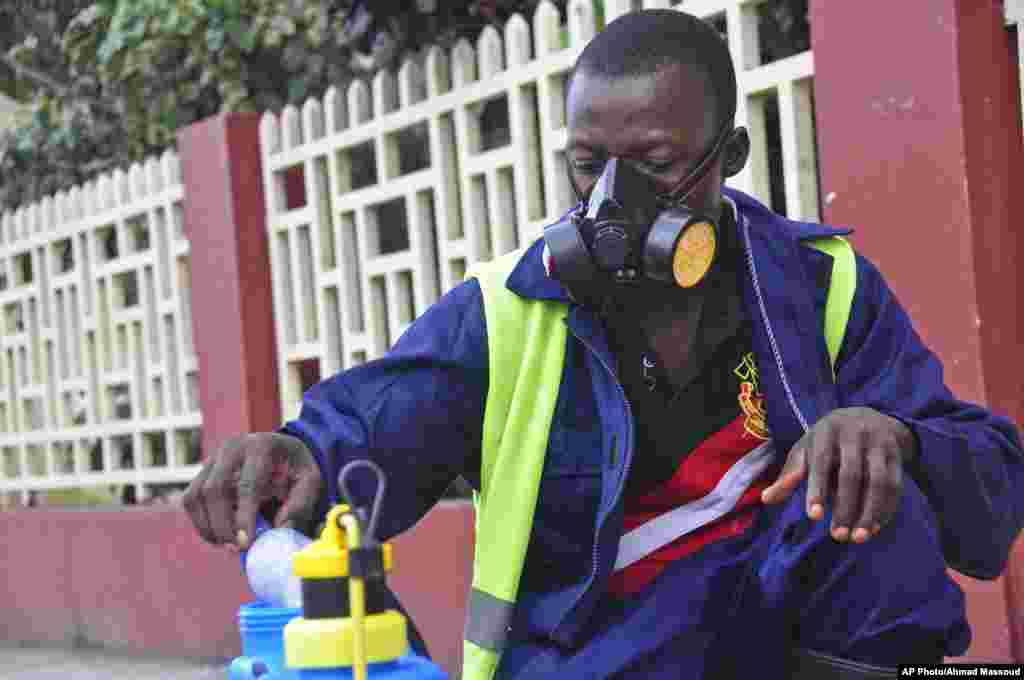 An employee of the Monrovia City Corporation mixes disinfectant before spraying it on the streets to prevent the spread of the deadly Ebola virus, Monrovia, Liberia, August 1, 2014.