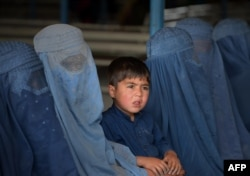 FILE - Afghan refugee families wait to be registered at the United Nations High Commissioner for Refugees (UNHCR) repatriation center on the outskirts of Peshawar, April 27, 2017.