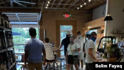 Patrons at a coffee shop in the trendy NoDa neighborhood of Charlotte, NC, wear masks. (Salim Fayeq/VOA)