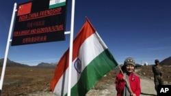 2012年10月21日一名印度女子在中國和印度位於海拔4700米的布姆拉兩國邊境之間舉起印度國旗給記者拍照。