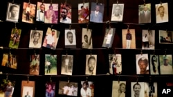 FILE - Family photographs of some of those who died hang in a display in the Kigali Genocide Memorial Centre in Kigali, Rwanda, April 2014. Officials said Rwandan Ladislas Ntaganzwa was arrested by Interpol agents in Congo, Dec. 7, 2015.