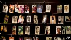 FILE - Family photographs of some of those who died hang in a display in the Kigali Genocide Memorial Centre in Kigali, Rwanda.