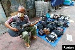 Seorang pedagang kaki lima (PKL) bermain gitar sambil menunggu pembeli di Jakarta (foto: dok). Pemerintah akan memberikan bantuan untuk warung dan PKL.