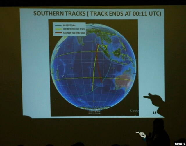 FILE - Malaysian Lieutenant General Ackbal Samad shows a map showing possible track of flight MH370 to relatives of passengers during a briefing by the Malaysian government at the Lido Hotel in Beijing, March 26, 2014.
