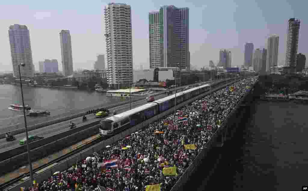 Thai anti-government protesters march cross Takin Bridge during a rally, Dec. 22, 2013, in Bangkok, Thailand.