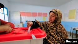 Seorang perempuan Tunisia memberikan suaranya di Tunis, 21 Desember 2014.