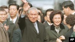 FILE - Former South Korean President Roh Tae-woo, with his wife, Kim Ok-sook, standing beside him, waves to supporters and neighbors after he was released from the Seoul prison in a special amnesty, Dec. 22, 1997.