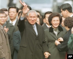 FILE - A smiling former South Korean President Roh Tae-woo, with his wife Kim Ok-sook standing beside him, waves to his supporters and neighbors upon arrivial at his home after he was released from the Seoul prison in a vspecial amnesty, Dec. 22, 1997.