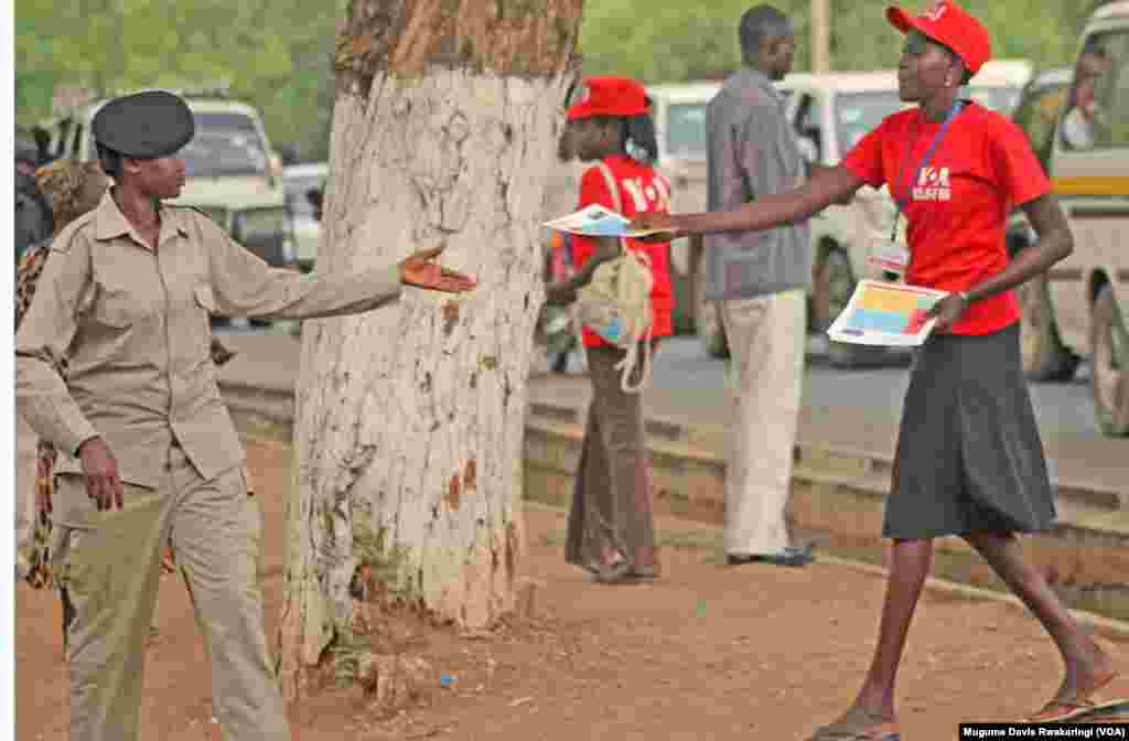 A young woman hands out a flier to another woman, in uniform, announcing the official launch of a new FM transmitter for Voice of America programs in Juba, South Sudan. The new transmitter allows some 400,000 residents of the South Sudanese capital to hea
