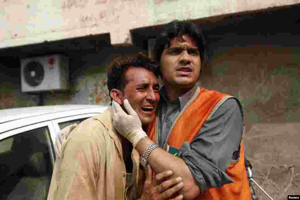 A rescue worker comforts a man as he cries over the death of his brother, who was killed in a bomb blast, at a hospital in Peshawar, Paksitan, Sept. 27, 2013.