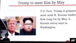Mtu anapita mbele ya bango linalo onyesha picha ya Rais Donald Trump na Kiongozi wa Korea Kaskazini Kim Jong Un mjini Tokyo, Japan Machi 9, 2018.