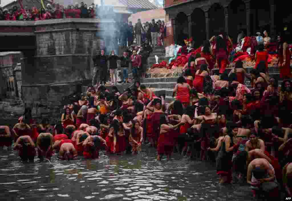 សាសនិកហិណ្ឌូក្នុងប្រទេសនេប៉ាល់មុជទឹកនៅក្នុងទន្លេបរិសុទ្ធ Bagmati នៅព្រះវិហារ Pashupatinath អំឡុងពិធីបុណ្យ Swasthani ដែលមានរយៈពេលជាច្រើនខែក្នុងទីក្រុង Kathmandu កាលពីថ្ងៃទី០៤ ខែកុម្ភៈ ឆ្នាំ២០១៩។
