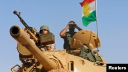 Dua tentara Peshmerga siaga di atas tank mereka di kota Mosul, Irak (foto: dok).