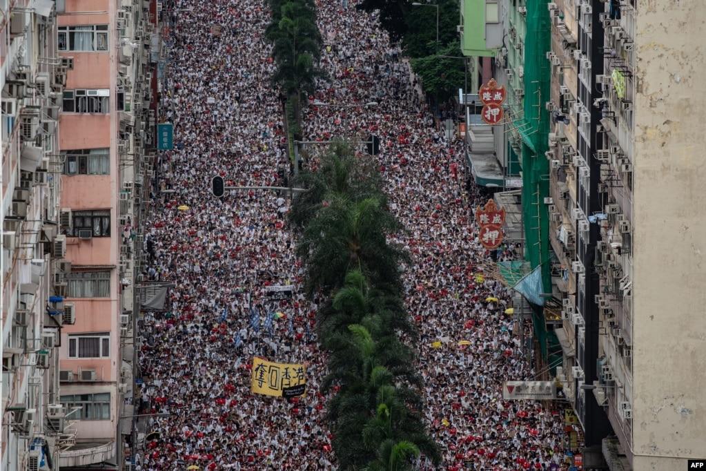 Протестующие маршируют во время митинга против спорного предложения закона об экстрадиции в Гонконге. Огромные протестные толпы толпились в Гонконге, когда гнев набухает над планами разрешить экстрадицию в Китай, предложение, которое вызвало самую большую общественную реакцию против про-пекинского руководства города за последние годы.
