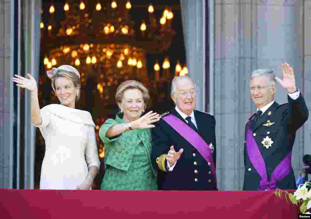 King Philippe (R) of Belgium and Queen Mathilde (L) salute the crowd together with King Albert II and Queen Paola from the balcony of the Royal Palace in Brussels, July 21, 2013.