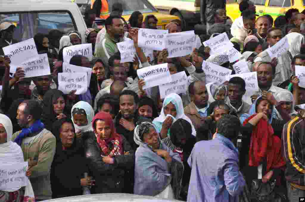 "Ethiopians carry posters in Amharic reading ""Meles We Love You"" as they gather to mourn as the body of the late Prime Minister Meles Zenawi arrived in Addis Ababa, August 22, 2012."