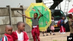 A child plays with an umbrella bearing the portrait of Zimbabwean President Emmerson Mnangagwa, at a public school in Harare, Feb. 5, 2019. Public teachers are alleging intimidation as they try to launch a nationwide strike for better salaries.