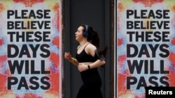 A person runs past posters with a message of hope, as the spread of the coronavirus disease (COVID-19) continues, in Manchester, Britain, April 12, 2020.