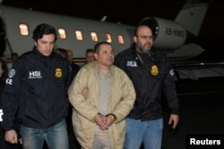 "FILE - Mexico's top drug lord Joaquin ""El Chapo"" Guzman is escorted as he arrives at Long Island MacArthur airport in New York, Jan. 19, 2017, following his extradition from Mexico."