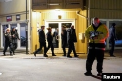 Police officers investigate at the scene where an arrow was shot into a wall after several people were killed and others were injured by a man using a bow and arrows to carry out attacks, in Kongsberg, Norway, October 13, 2021.