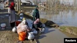 Phụ nữ lấy nước uống từ một đường ống dẫn nước của thành phố ở ngoại ô Srinagar, Ấn Độ, ngày 22/3/2015.