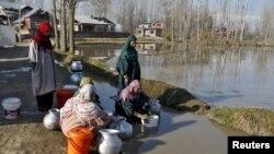 ແມ່ຍິງອິນເດຍຄົນນຶ່ງ ພວມໂຕ່ງເອົານ້ຳດື່ມ ໃສ່ພາສະນະ ຈາກທໍ່ນ້ຳເທດສະບານ ໃນຂະນະທີ່ແມ່ຍິງຄົນອື່ນກຳລັງຢືນລໍຖ້າພຽນຂອງຕົນ ຢູ່ທີ່ນອກເມືອງ Srinagar, ວັນທີ 22 ມີນາ 2015. ວັນທີ 22 ມີນາ ແມ່ນຖືກກຳນົດໃຫ້ເປັນ ວັນນ້ຳຂອງໂລກ ໂດຍ UN.