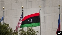 The pre-Gadhafi Libyan flag flies in front of the United Nations headquarters during the 66th session of the General Assembly at United Nations headquarters in New York, Sept. 20, 2011.