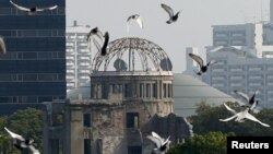 Burung merpati beterbangan di atas Taman Memorial Perdamaian di Hiroshima dengan Kubah Bom Atom pada latar belakang.