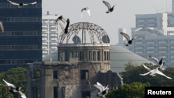 FILE - Doves fly over Peace Memorial Park with the Atomic Bomb Dome in the background, at a ceremony in Hiroshima, Japan, Aug. 6, 2015.
