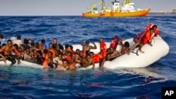 Para migran Afrika dengan perahu karet minta bantuan kapal untuk menolong mereka di perairan dekat pulau Lampedusa, Italia hari Minggu (17/4). Ratusan migran Afrika dilaporkan tenggelam pada 8 April lalu.