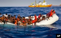 FILE - Migrants ask for help from a dinghy boat as they are approached by the SOS Meditrranee's ship Aquarius, background, off the coast of the Italian island of Lampedusa, April 17, 2016.
