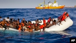 FILE - Migrants ask for help from a dinghy boat as they are approached by the SOS Mediterranee's ship Aquarius, background, off the coast of the Italian island of Lampedusa, April 17, 2016.