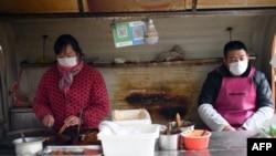 2020年1月26日,北京一家餐館員工戴口罩進行食品操作。