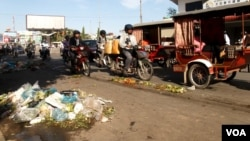Piles of garbage, mostly plastic bags, are scattered on a road near Derm Kor Market, Phnom Penh, Cambodia, July 3, 2015. (Ouch Nida/VOA Khmer)