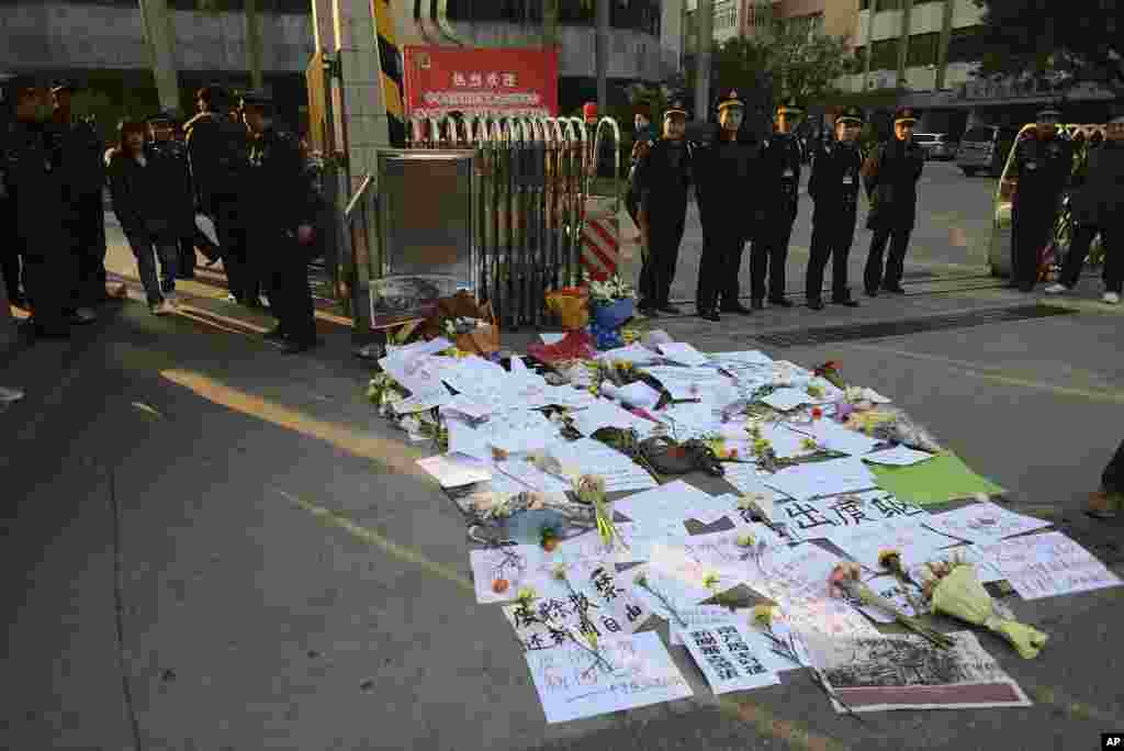 Security guards stand near protest banners and flowers are laid outside the headquarters of Southern Weekly newspaper, January 7, 2013.