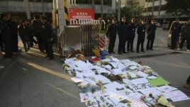 Security guards stand near protest banners and flowers are laid outside the headquarters of Southern Weekly newspaper in Guangzhou, Guangdong province January 7, 2013.