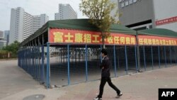 This picture taken on February 22, 2013 shows a man walking past empty tents in a Foxconn recruitment center in Shenzhen, south China's Guangdong province.