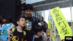 香港市民劉太太帶同一對9歲及7歲的子女參與雨傘運動一周年活動。 (美國之音特約記者湯惠芸照)