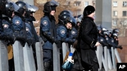 A woman walks past as Ukrainian riot police stand at the entrance of the regional administrative building in Donetsk, Ukraine, March 7, 2014.