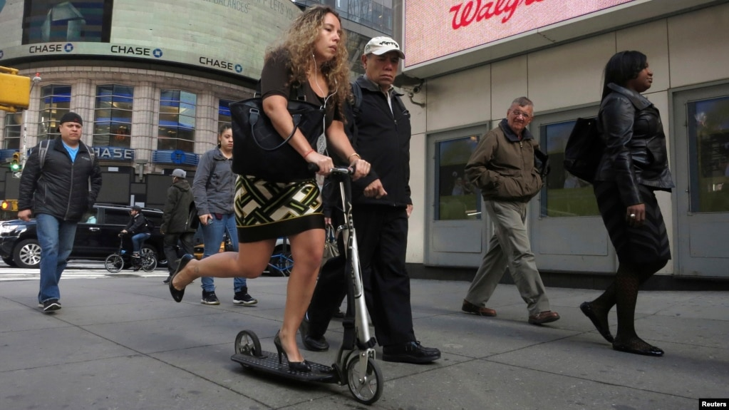 A women rides a scooter along 42nd Street in New York.