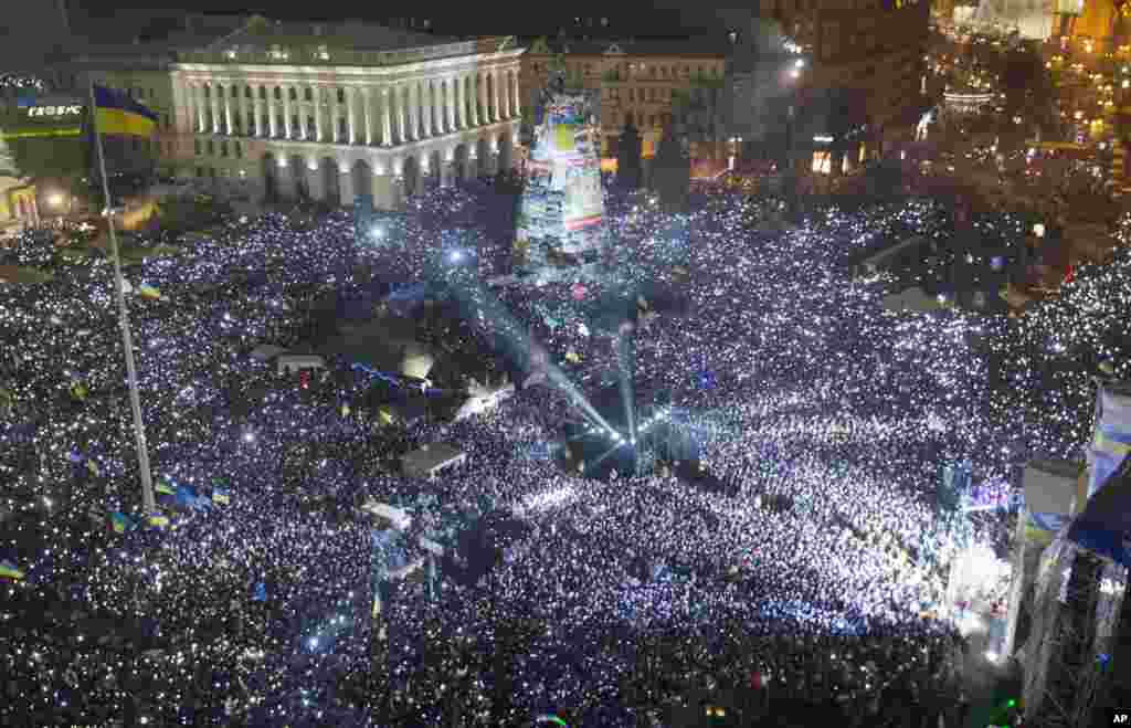 Pro-European Union activists hold lights as they sing the Ukrainian national anthem, celebrating the New Year in Kyiv, Ukraine, Jan. 1, 2014.
