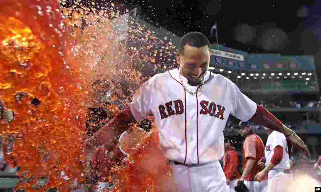 Boston Red Sox's Mookie Betts is doused after his walk-off two-run double during the ninth inning of a baseball game against the St. Louis Cardinals in Boston.