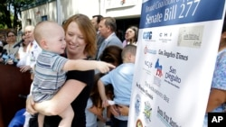 Jennifer Wonnacott holds her son Gavin as he points to a sign showing support of a measure requiring nearly all California school children to be vaccinated, at a news conference after the bill was signed by Gov. Jerry Brown, June 30, 2015, in Sacramento, California.