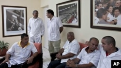 Cuban doctors, who will travel to Liberia and Guinea, wait for the start of a press event in Havana, Oct. 21, 2014.