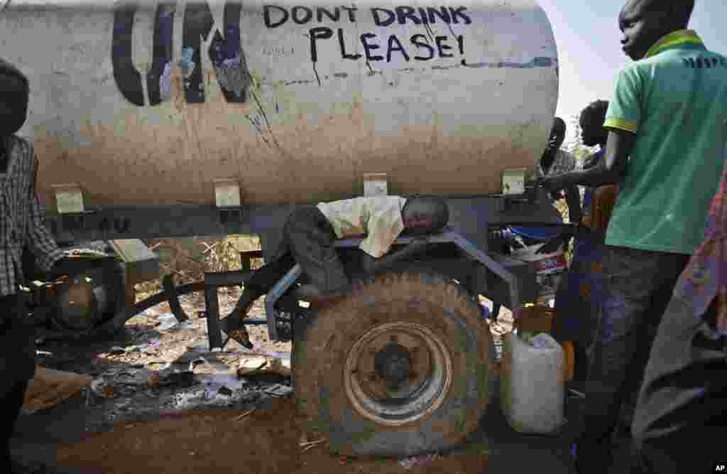 A young displaced boy rests on the wheel arch of a water truck while others fill containers from it, at a United Nations compound on the outskirts of Juba, the South Sudanese capital.